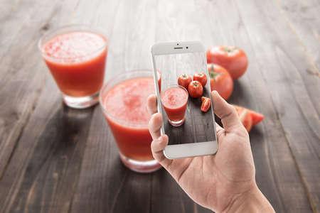 licuadora: Foto Tomar de batido de verduras de tomates maduros rojos en mesa de madera
