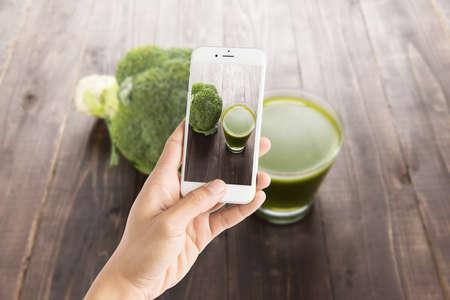 tomando refresco: Tomar la foto de jugo de brócoli en la mesa de madera