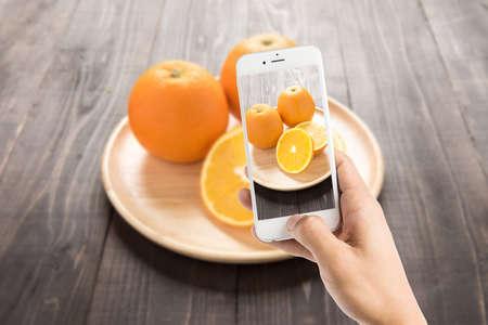 tomando refresco: Tomar la foto de naranjas frescas en un plato de madera, frutas frescas sobre fondo de madera Foto de archivo