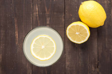 the juice: Top view lemonade with fresh lemon on wooden background.