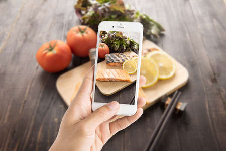 Taking photo of grilled salmon on cutting board on wooden background