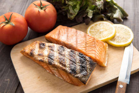 Grilled salmon on cutting board on wooden background photo