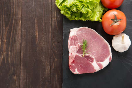 Top view raw pork on blackboard and vegetables on wooden background.