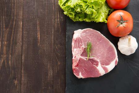 carniceria: Vista superior de cerdo cruda en la pizarra y verduras en el fondo de madera.