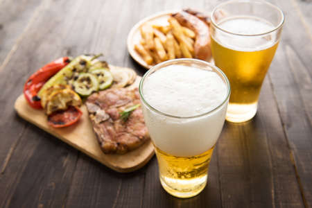Beer in glass with gourmet steak and french fries on wooden background.