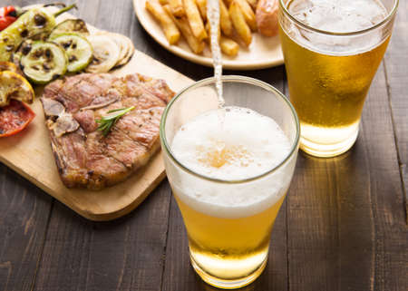 food: Beer being poured into glass with gourmet steak and french fries on wooden background. Stock Photo