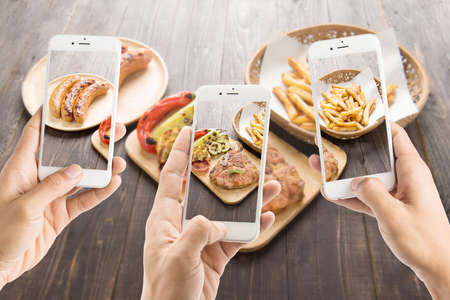 the photo: friends using smartphones to take photos of sausage and pork chop and french fries.