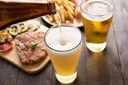 Bier in glas wordt gegoten met gastronomische biefstuk en patat op houten achtergrond.