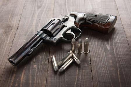 pistola: pistola rev�lver negro con balas aisladas en el fondo de madera. Foto de archivo