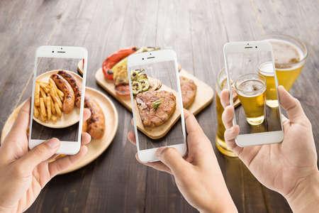 food: 스마트 폰을 사용하는 친구는 소시지와 돼지 고기와 맥주의 사진을 촬영합니다.