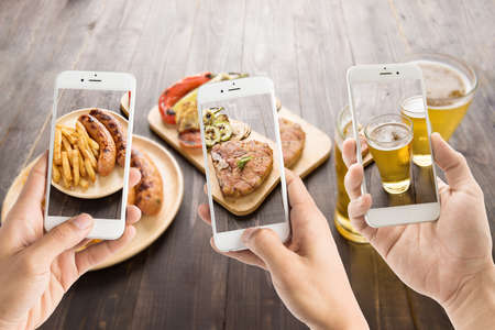 restaurant people: friends using smartphones to take photos of sausage and pork chop and beer.