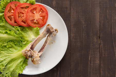 pauper: Bone chicken and vegetable on wooden background Stock Photo