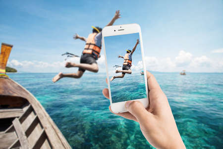 thailand: Taking photo of snorkeling divers jump in the water Stock Photo