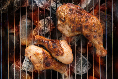 grill chicken: Grilled chicken thigh over flames on a barbecue