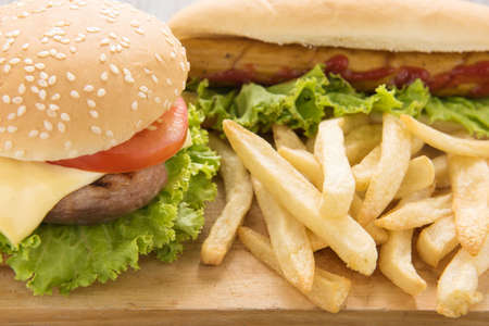 hamburger: Hot dogs,hamburgers and french fries on the wooden background Stock Photo