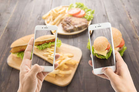 Friends using smartphones to take photos of hot dog and hamburger Banco de Imagens