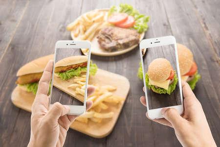 Vrienden met smartphones om foto's van hot dog en hamburger te nemen