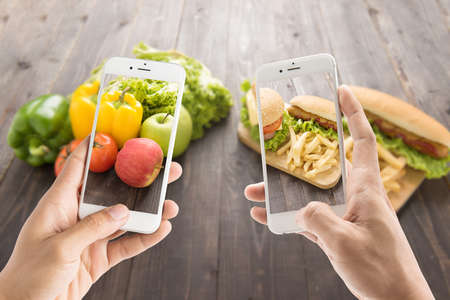 contrasting: Friends using smartphones to take photos with contrasting food Stock Photo
