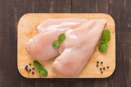 Raw chicken breast fillets on wooden background.