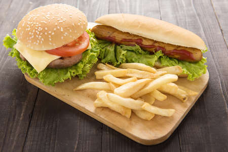 sausage dog: Hot dogs,hamburgers and french fries on the wooden background Stock Photo