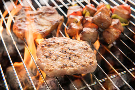 seasoned: Assorted delicious grilled meat over the coals on a barbecue Stock Photo