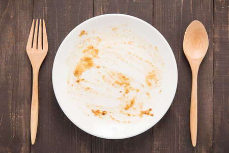 leftover: Empty dish after food on the wooden background.