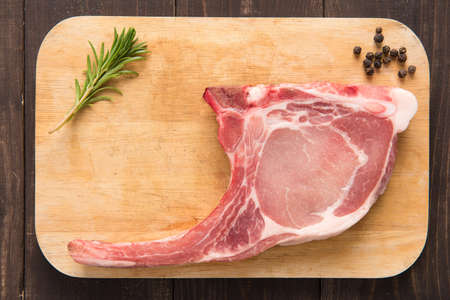 Fresh pork chops and pepper on wooden background. photo