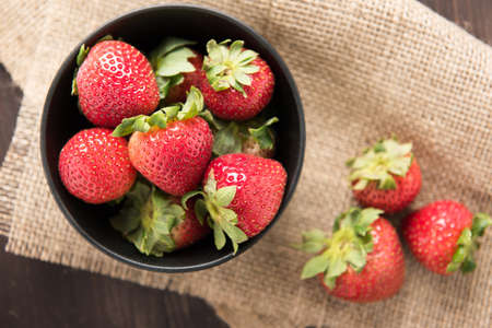 Top view fresh strawberries in a bowl on wooden background photo