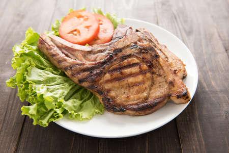 pork chop: Grilled steak with vegetables on a wooden background