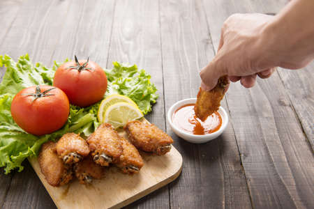 drum sticks: Hand dunk chicken hot wings in dipping sauce on wooden