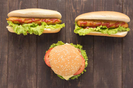 hotdogs: Hot dogs and hamburgers on the wooden background