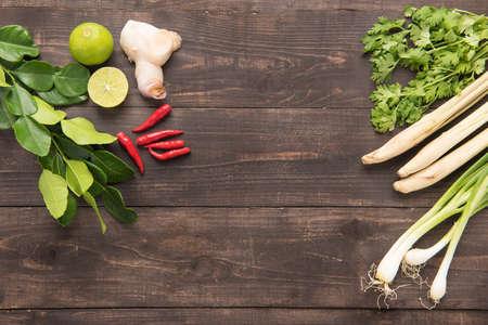 コブミカンの葉、コリアンダーやコリアンダー、ジンジャー、レモン、レモングラス、赤唐辛子、木製の背景に青ネギ。オーバーヘッドのビュー。