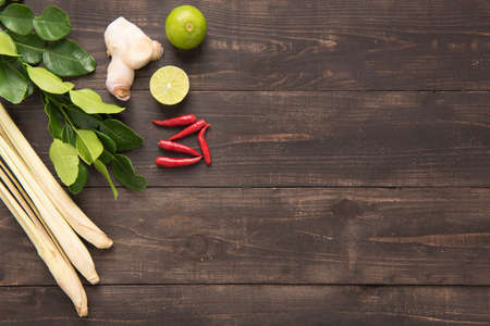 thai pepper: Kaffir lime leaves, Ginger, lemon, Red chilli and Green onions on wooden background. Overhead view.