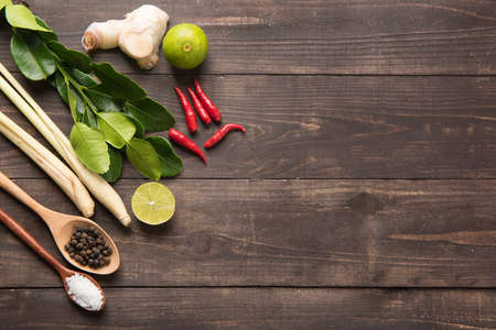 ingredient: Kaffir lime leaves, Ginger, lemon, Pepper, Salt,  Red chilli and Green onions on wooden background. Overhead view.