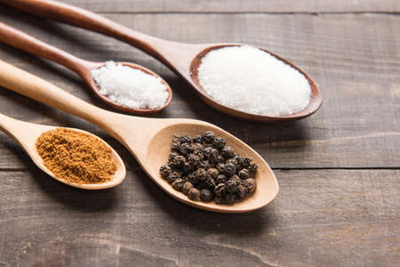 dried herbs: collection set of spices on wooden spoons ( Black pepper, salt , paprika, sugar)