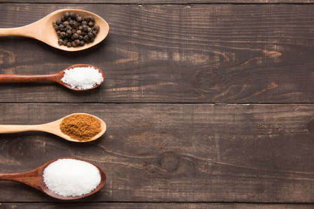 collection set of spices on wooden spoons ( Black pepper, salt , paprika, sugar)