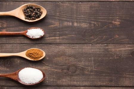 pepe nero: collezione insieme di spezie su cucchiai di legno (pepe nero, sale, peperoncino, zucchero) Archivio Fotografico