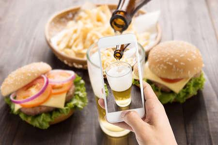 cerveza: El uso de teléfonos inteligentes para tomar fotos de la cerveza que se vierte en el vidrio con hamburguesas gourmet