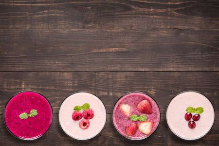 smoothies: Conjunto de batido de frutas en copas sobre fondo de madera