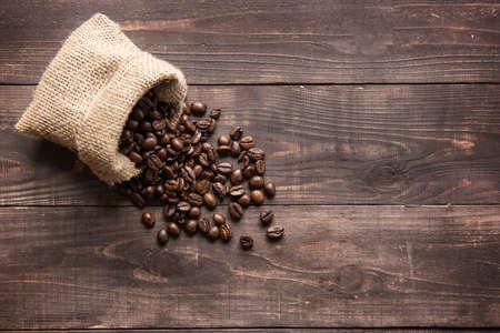 コーヒー豆をその空スペースおよび木製の背景
