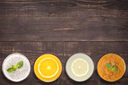 jugos: Conjunto de batido de frutas y jugo en copas sobre fondo de madera con un montón de espacio de la copia para el texto o la edición. Foto de archivo