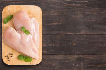 brasiere: Filetes de pechuga de pollo sin procesar en el fondo de madera con un mont�n de espacio de la copia para el texto o la edici�n.