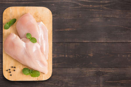 Raw chicken breast fillets on wooden background with a lot of copy space for your text or editing.