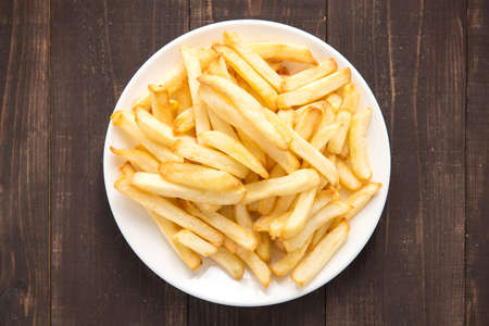 french fries plate: French fries on white dish on wooden background.