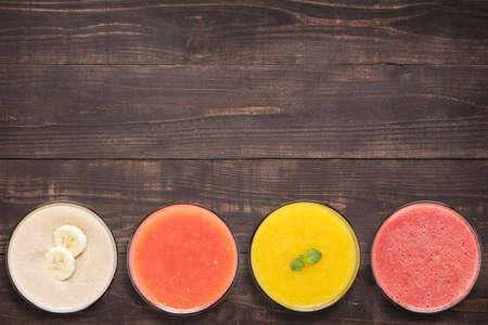 licuado de platano: Conjunto de batido de frutas y jugo en copas sobre fondo de madera con un montón de espacio de la copia para el texto o la edición. Foto de archivo
