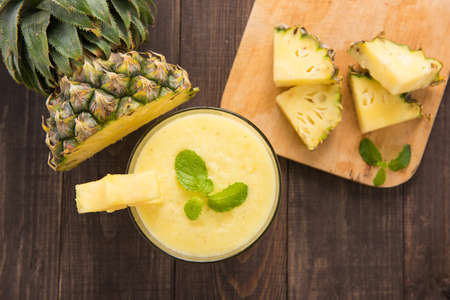pineapple  glass: Pineapple smoothie with fresh pineapple on wooden table.