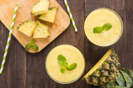 mango slice: Pineapple smoothie with fresh pineapple on wooden table.