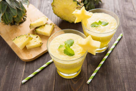 mangoes: Pineapple smoothie with fresh pineapple on wooden table.