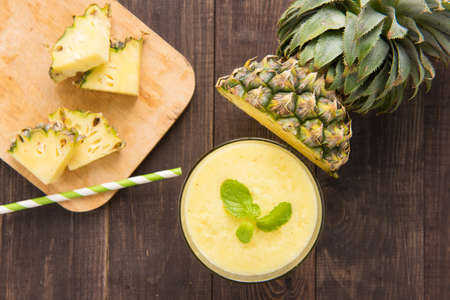 Pineapple smoothie with fresh pineapple on wooden table.