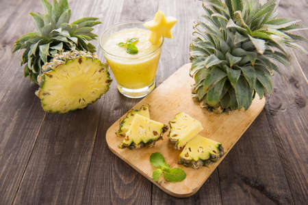 pineapple  glass: Fresh pineapple with pineapple smoothie on wooden table. Stock Photo